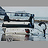 Car upside down on beach.